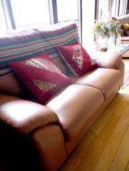 茶色のソファには赤色のクッションを